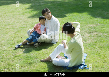 Family sitting on grass, woman taking photo of man and boy - Stock Photo