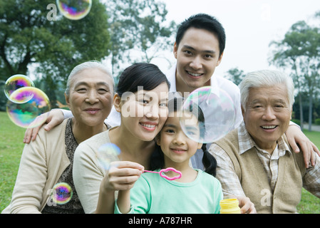 Three generation family in park blowing bubbles, portrait - Stock Photo