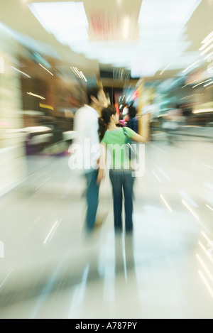 Couple walking through shopping mall, rear view, full length, blurred motion - Stock Photo