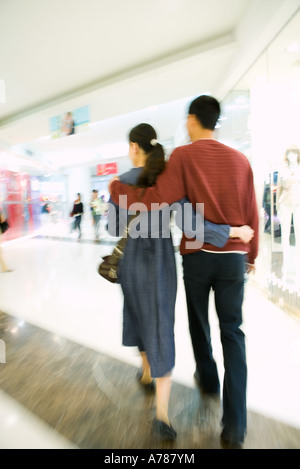 Couple walking through shopping mall, rear view, full length - Stock Photo