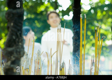 Incense burning, couple standing in blurred background - Stock Photo