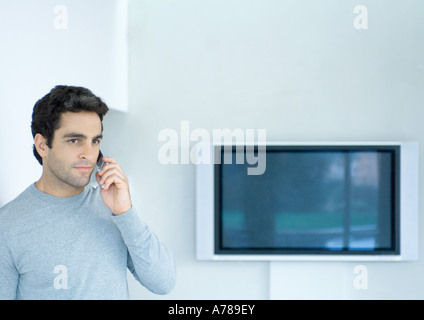 Man using phone, widescreen TV in background - Stock Photo