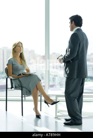 Businessman speaking to woman sitting in lobby - Stock Photo