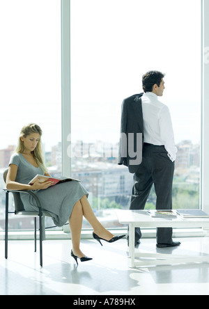 Waiting room, woman sitting reading magazine while man looks out window - Stock Photo