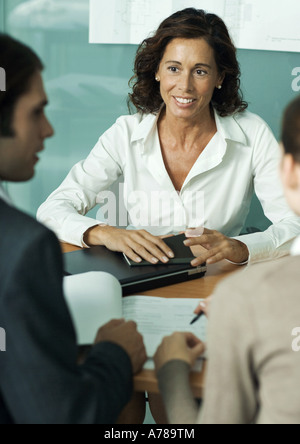 Mature female professional sitting across from clients, smiling - Stock Photo