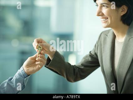 Professional woman handing man set of keys