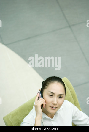 Female executive sitting in armchair using cell phone, high angle view - Stock Photo