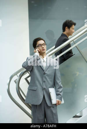 Businessman using cell phone near staircase - Stock Photo