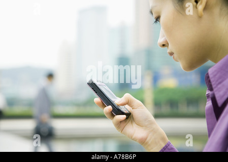 Businesswoman using messaging phone, close-up, side view - Stock Photo