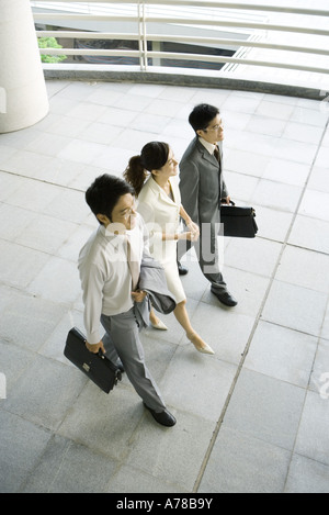 Three business executives walking side by side, high angle view - Stock Photo