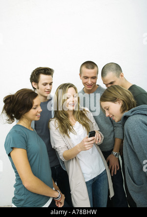 Group of young adult and teenage friends looking at cell phone, white background - Stock Photo