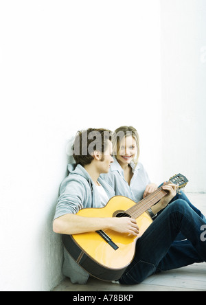 Young couple sitting on ground, man playing guitar - Stock Photo
