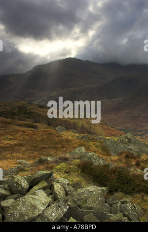 sun rays breaking through clouds above Wetherlam mountain in the Lake District - Stock Photo