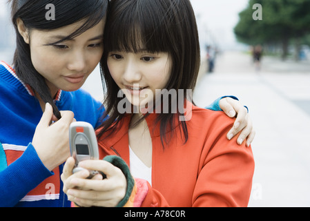 Two young women friends looking at cell phone together - Stock Photo