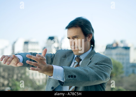 Businessman holding arms out in front of him and pointing, looking out of frame - Stock Photo