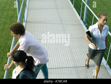 Teenage couple leaning against rail of walkway while businesswoman walks by - Stock Photo