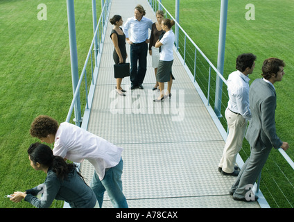 People standing in small groups on walkway, high angle view - Stock Photo