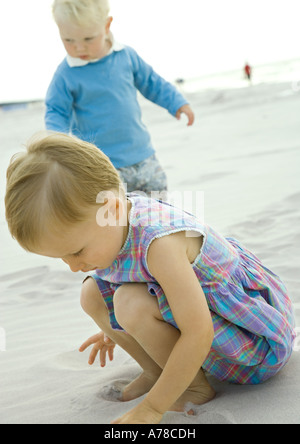 Two toddlers playing on beach - Stock Photo