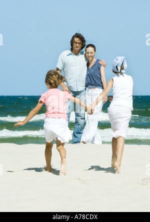Family on beach, two girls walking hand in hand toward parents - Stock Photo