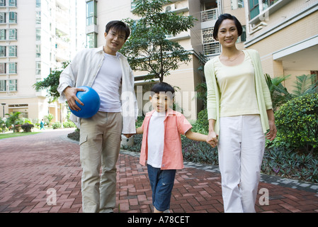 Family standing by apartment complex, smiling at camera, father holding ball - Stock Photo