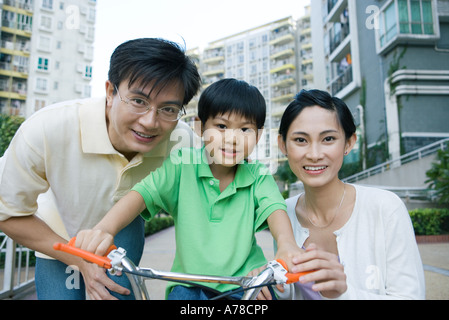 Boy on bicycle, between parents, portrait - Stock Photo