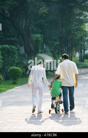 Boy riding bicycle with training wheels, parents on either side, rear view - Stock Photo