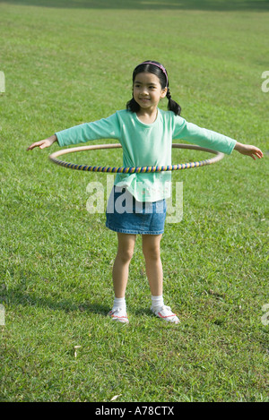 Girl playing with plastic hoop - Stock Photo