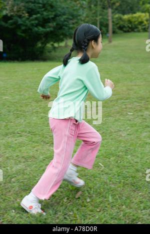 Little girl running across grass - Stock Photo