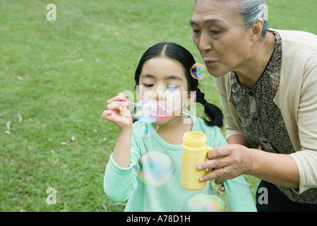 Little girl and grandmother blowing bubbles - Stock Photo