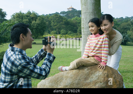 Man filming wife and daughter in park with video camera - Stock Photo