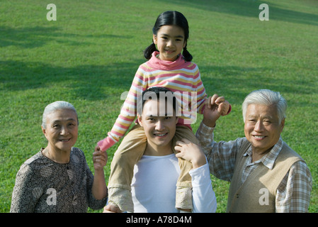 Three generation family, girl sitting on father's shoulders, holding grandparent's hands, portrait