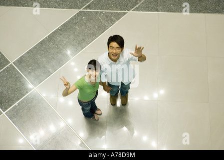 Young couple standing on star pattern, looking up at camera, high angle view - Stock Photo