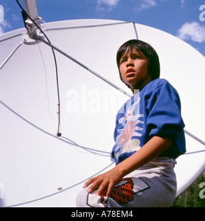 A Canadian First Nations Interior Salish boy teenager standing in front of a satellite dish at his Lillooet home - Stock Photo