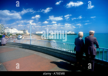 Two elderly people staring out to sea from the promenade at Eastbourne Sussex UK - Stock Photo