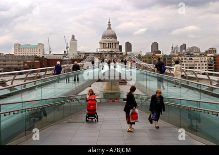 UK London pedestrians crossing Millennium Bridge over River Thames near St Pauls Cathedral - Stock Photo