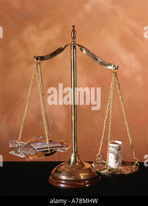 Pan balance set up as concept image to illustrate the challenge being made to traditional cash transactions by credit - Stock Photo
