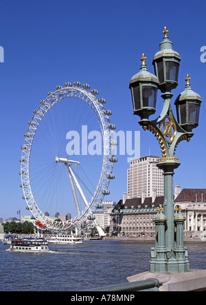 London Westminster Bridge ornate three lamp cluster on parapet with River Thames British Airways millennium Ferris - Stock Photo
