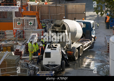 London congested building site compound with readymix concrete delivery truck & workmen in high visibility health - Stock Photo