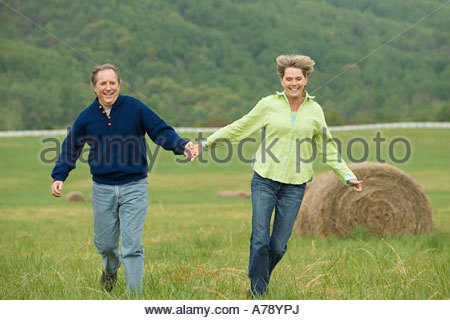 Mature couple running in field - Stock Photo