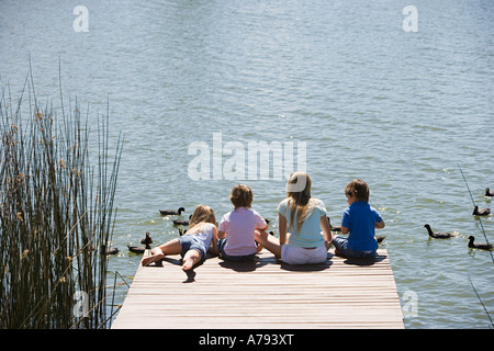 Children feeding ducks on a lake - Stock Photo