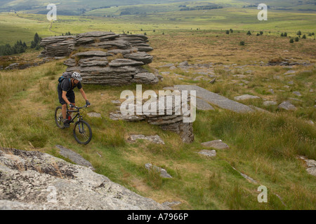 Mountain Bike rider rides a Singletrack path on Dartmoor. - Stock Photo