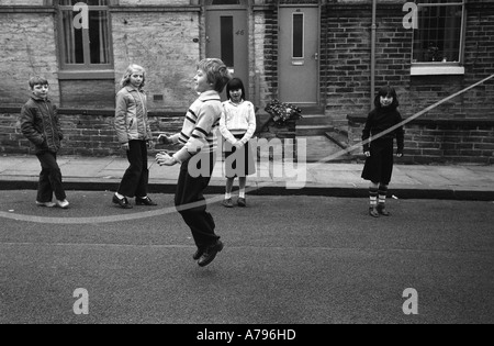 Children kids playing together skipping in the street Saltaire Bradford Yorkshire UK  1981 HOMER SYKES - Stock Photo