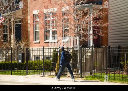 CHICAGO Illinois African American boy with backpack walk past red brick single family homes street in Old Town neighborhood - Stock Photo
