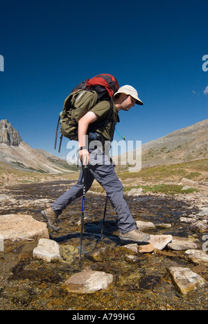 Young Man 20 25 jumping across an alpine creek on the Skyline Trail in Japser National Park Alberta - Stock Photo