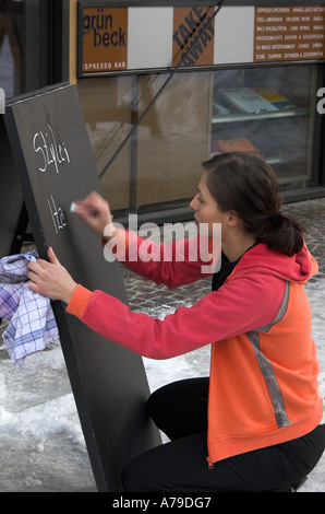 A young female writing on a blackboard outside a restaurant, ski resort of St. Anton am Arlberg, Tirol, Austria - Stock Photo