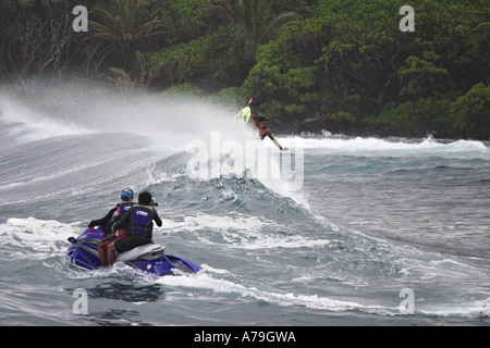 Two people on a seadoo film a male surfer about to flip out on a big wave Isaac Hale Beach Park Puna Big Island - Stock Photo