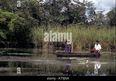Local guys out in rough wooden canoe looking for fish near Lamanai New River Belize No MR - Stock Photo
