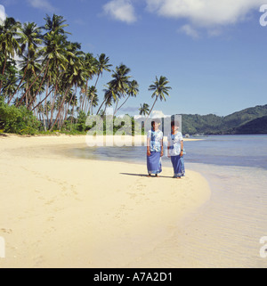 Two Fijian ladies in long flowered dresses on tropical beach on Matagi Island The Fijian Islands - Stock Photo