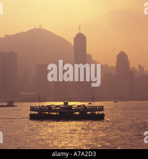 The famous Star ferry sails along hazy waterfront of Central District at dusk with Victoria Peak Hill beyond Hong - Stock Photo