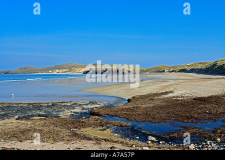 Walkers on beach in Balnakeil Bay near Durness in Sutherland Scotland with Faraid Head behind - Stock Photo